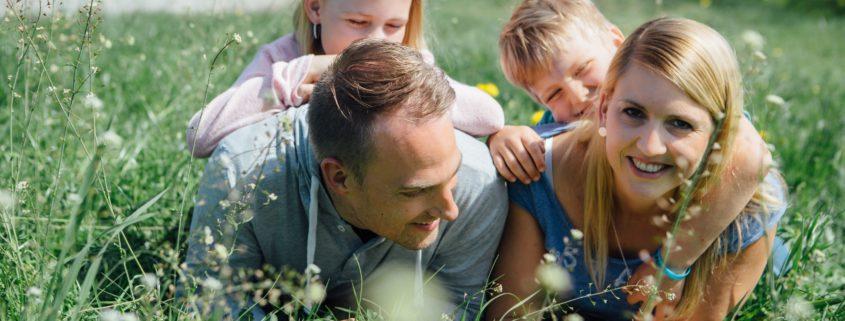 Familie welche im Gras rumalbert.