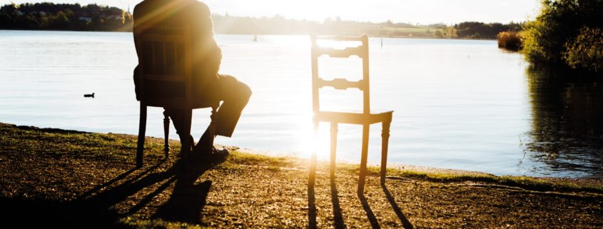 Mann sitzt an See neben leerem Stuhl